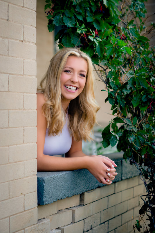 Blonde girl leaning on brick for senior pictures