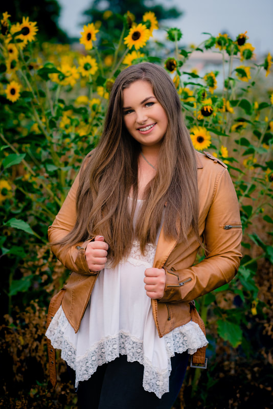 Girl in sunflower field wearing a tan leather jacket smiling for senior pictures
