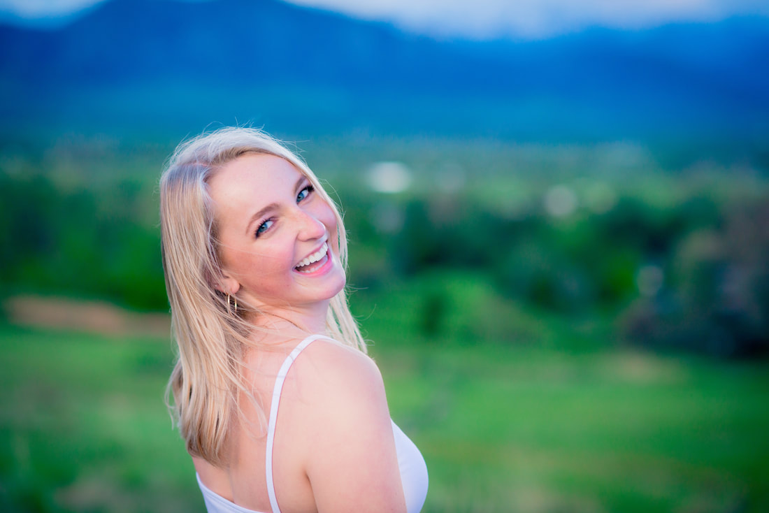A portrait of a young woman with blonde hair wearing a light-colored tank top, laughing and turning to face the camera, with green nature in the background.