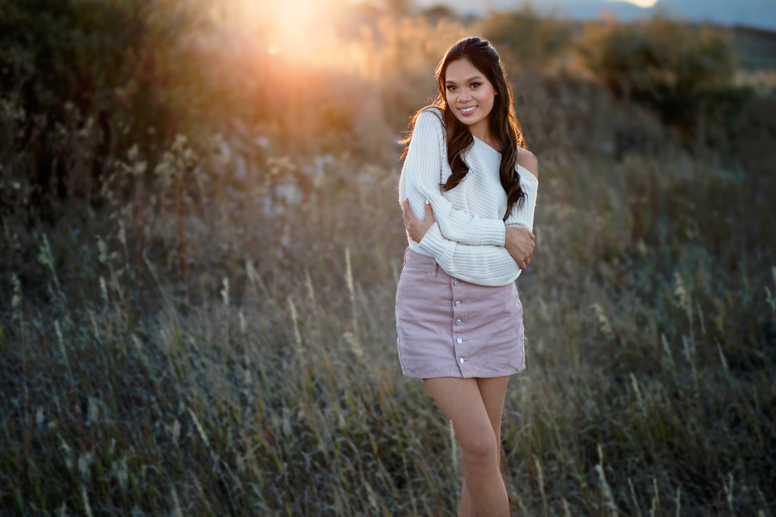 A portrait of a young woman standing in a field outside with her arms wrapped around herself, wearing a white sweater and a pink skirt.
