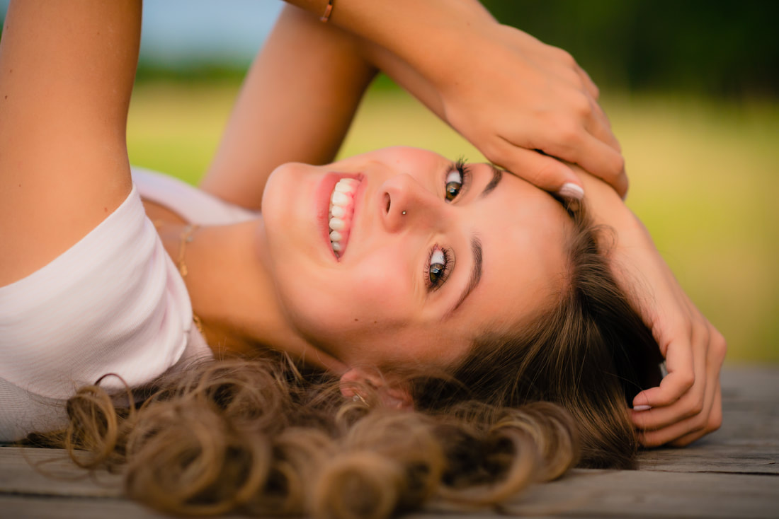 A portrait of a young woman lying down wearing a necklace, a white top, and with a nose piercing.