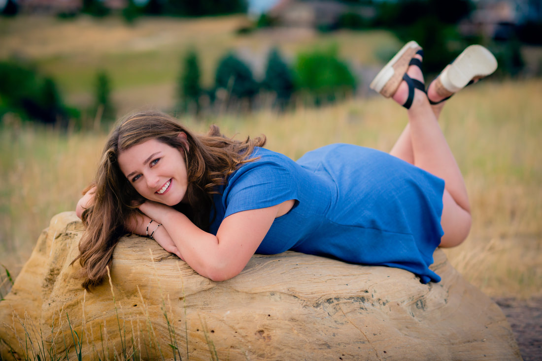 Girl in blue dress smiling at camera for senior pictures