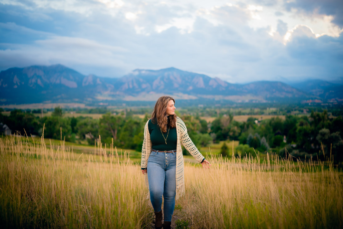 Girl walking through field with boulder flatirons in the background for senior pictures