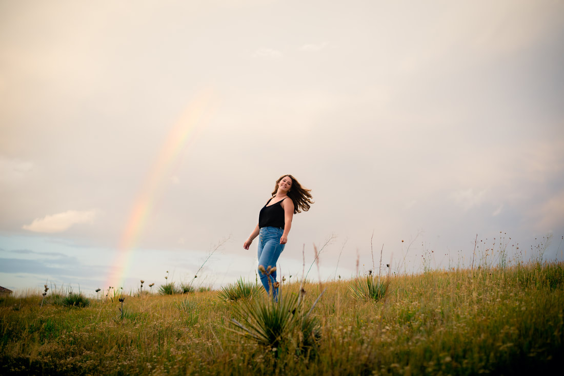 Brunette girl swinging her hair over her shoulder with a rainbow in the background for senior pictures