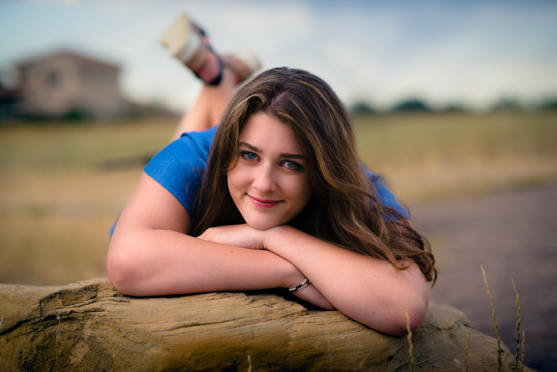 girl in blue dress laying on a rock for senior pictures